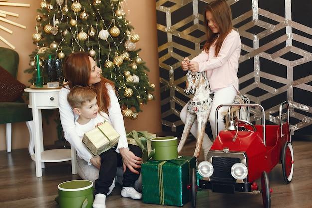 Madre con niños lindos cerca del árbol de navidad