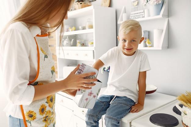 Madre con niños pequeños cocinando en casa