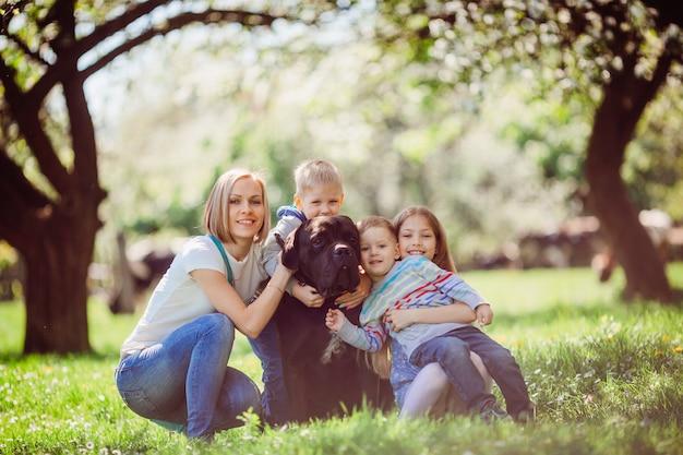 La madre, los niños y el perro sentado en la hierba