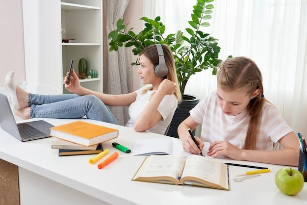 La madre no está ayudando a la hija a hacer la tarea mientras usa su teléfono inteligente y escucha música con auriculares