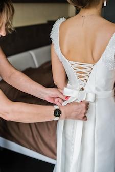 Madre de la novia ayuda a la novia a vestir un vestido.