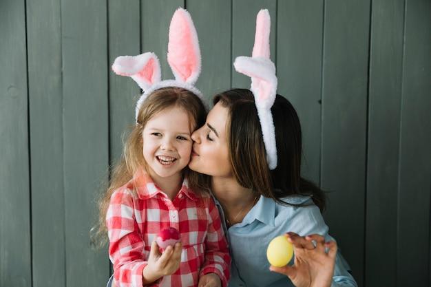 Madre en orejas de conejo besando a hija en mejilla
