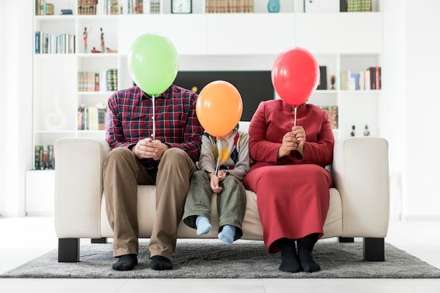 Madre padre y así escondiéndose detrás de globos en casa