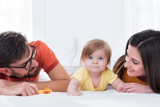 Madre y padre con bebé en la cama
