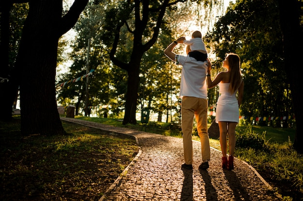 Madre y padre con un bebé en los hombros caminando en el parque verde