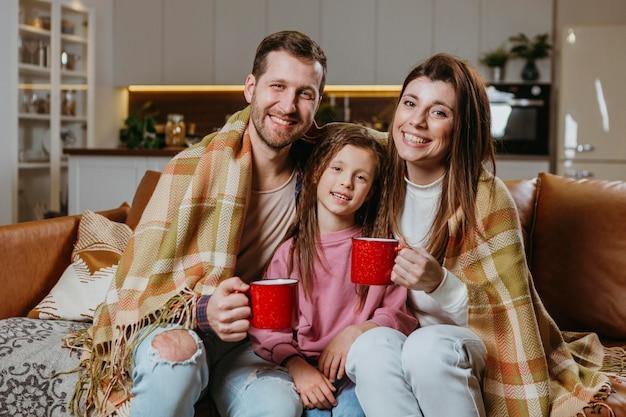 Madre y padre con bebidas calientes con mi hija en casa