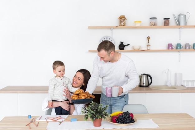 Madre y padre en la cocina con niño y espacio de copia