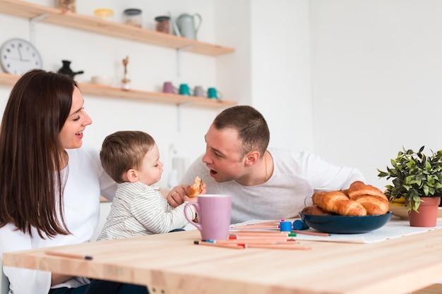 Madre y padre comiendo con bebé en la cocina