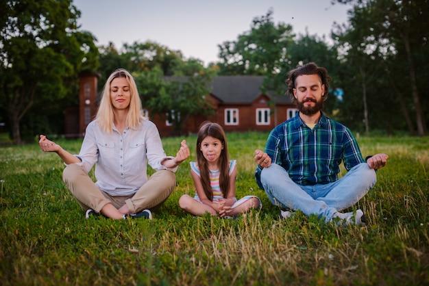 Madre padre e hija niño meditan juntos en posición de loto al aire libre.