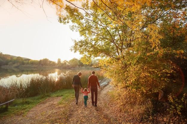 Madre padre e hija van por el sendero del bosque trío y van directamente al lago del bosque
