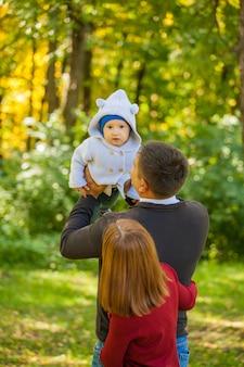 Madre, padre e hijo en un paseo por el parque.