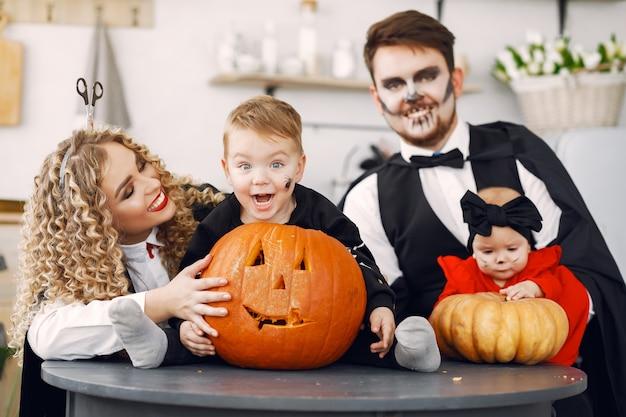 Madre padre e hijos en disfraces y maquillaje. la familia se prepara para la celebración de halloween.
