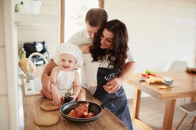 La madre, el padre y el hijo cocinando una carne