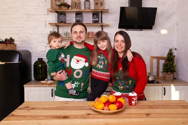Madre, padre, hijo e hija en la mañana de navidad en la cocina.