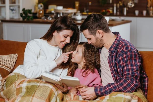 Madre y padre leyendo libro con hija en el sofá