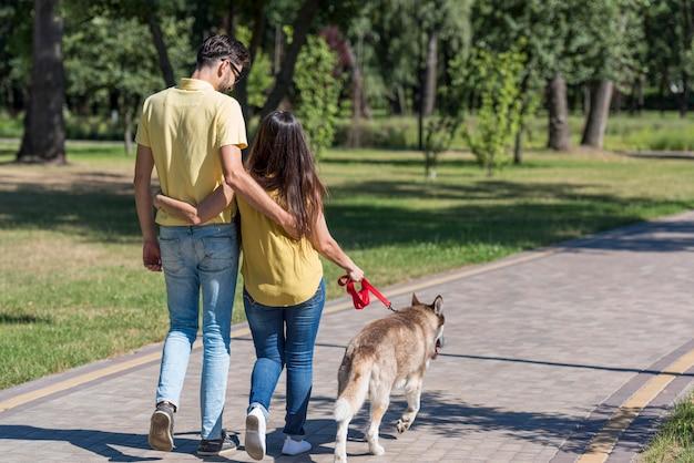 Madre y padre en el parque paseando al perro.