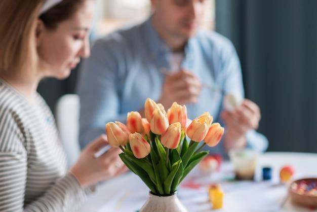 Madre y padre pintando huevos para pascua