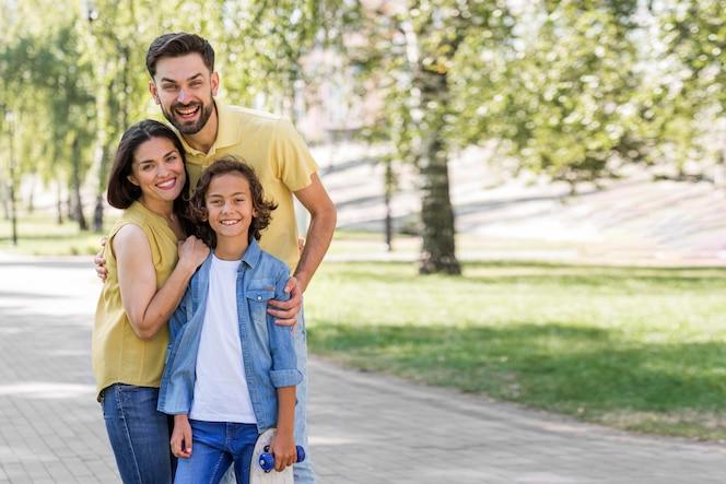 Madre y padre posando con su hijo en el parque.