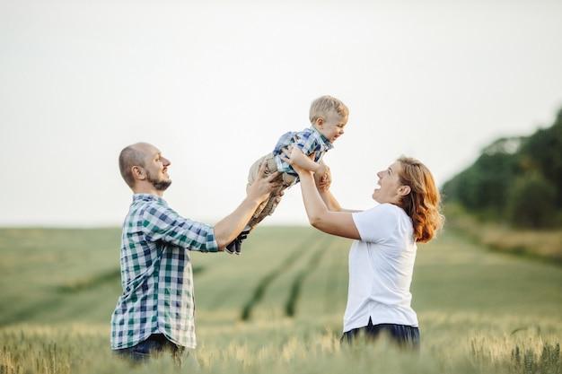 Madre y padre sostienen a su hijo parado en el campo