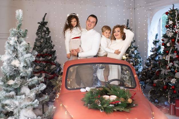 Madre y padre y sus hijos en coche rojo cerca de árboles de navidad.