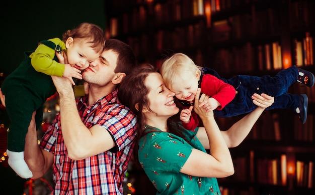 La madre y el padre tienen en las manos a sus hijos