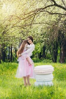 Madre y una pequeña hija caminan en la primavera apple floreciente