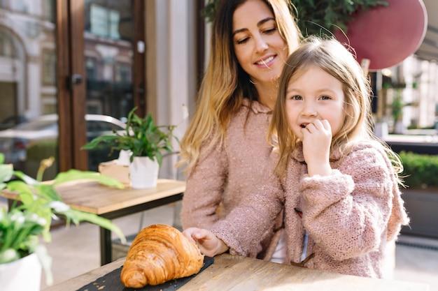 Madre con pequeña hija encantadora está sentada en la cafetería a la luz del sol