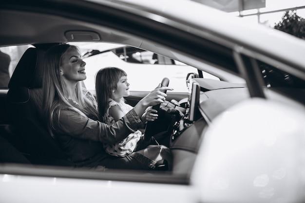 Madre con pequeña hija sentada en un automóvil en una sala de exposición de automóviles