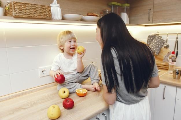 Madre con pequeño hijo comiendo frutas en una cocina