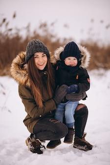 Madre con pequeño hijo en el parque de invierno
