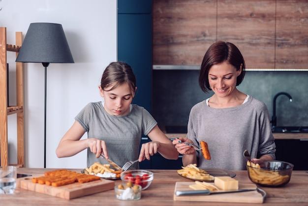 Madre de pie junto a la mesa en casa y sirviendo papas fritas