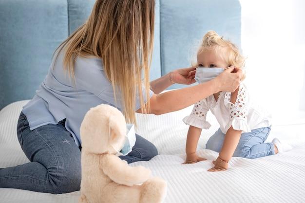 Madre poniendo máscara médica al niño en casa durante la cuarentena