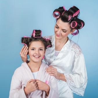 Madre poniendo rizador en el pelo de hijas
