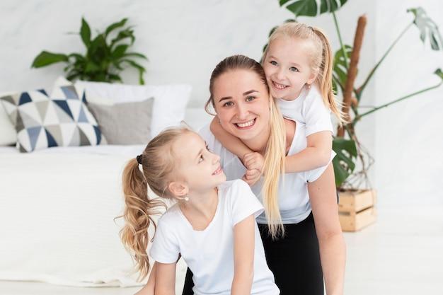 Madre posando felizmente con hijas en casa