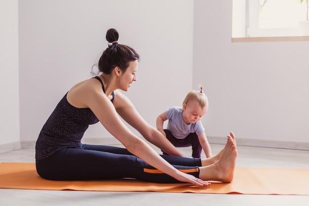 La madre practica yoga en casa con su hijo