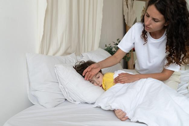 Madre preocupada comprobar la temperatura del niño enfermo con la mano niño enfermo con gripe o enfermedad covid dormir en la cama