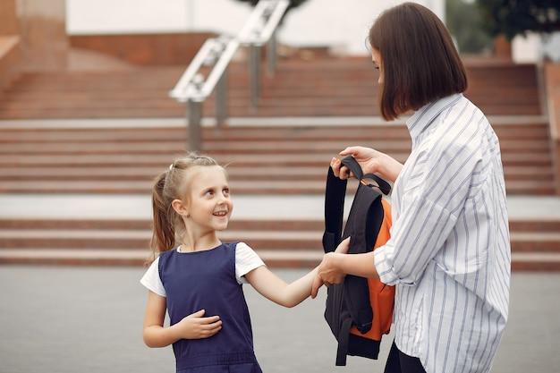 Madre prepara pequeña hija a la escuela