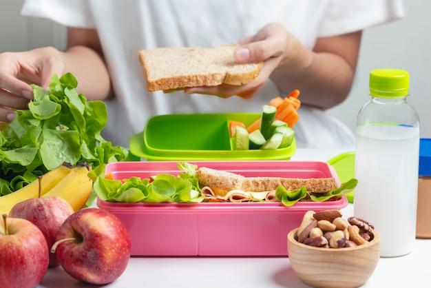 Madre preparando la caja de almuerzo escolar