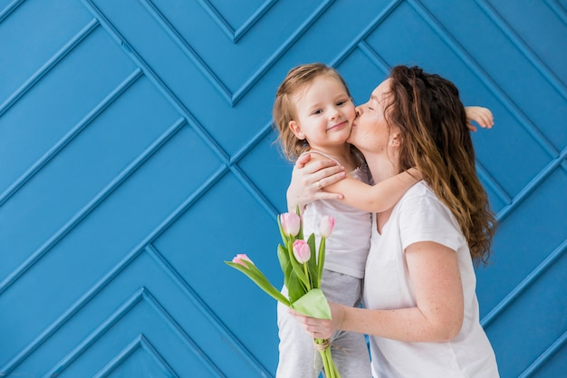 Madre que besa a su pequeña hija bonita que sostiene las flores del tulipán sobre fondo azul