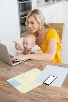 Madre que usa el ordenador portátil con el bebé en la cocina