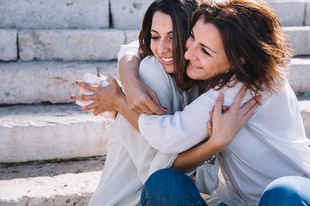 Madre con regalo abrazando a mujer