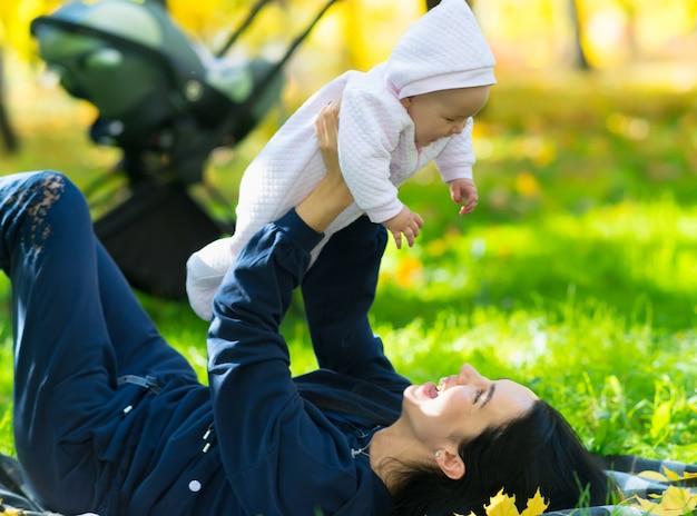 Madre riendo jugando con su hija mientras yace sobre una manta en un parque sobre la exuberante hierba verde