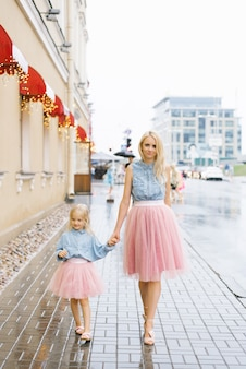 Madre rubia e hija pequeña con faldas rosadas y camisas de mezclilla. se toman de la mano y caminan bajo la lluvia en el verano en la ciudad