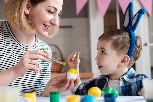 Madre rubia enseñando a su hijo a pintar huevos de pascua
