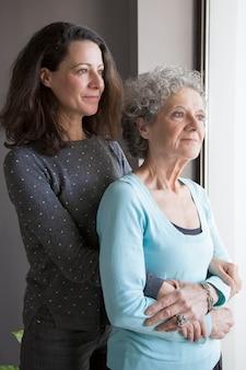 Madre senior pensativa tranquila y su hija mirando por la ventana
