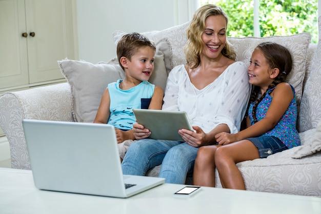 Madre sentada con hija e hijo usando tableta en sofá