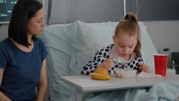 Madre sentada junto a su hija enferma mientras come el almuerzo recuperándose después de una cirugía médica. niño hospitalizado con nutrición de desayuno de alimentos saludables en la sala del hospital durante el examen