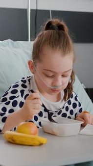 Madre sentada con su hija enferma mientras come comida sana en la sala del hospital
