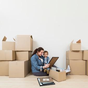 Madre sentada con su hijo mirando el marco de la foto desempacando las cajas de cartón