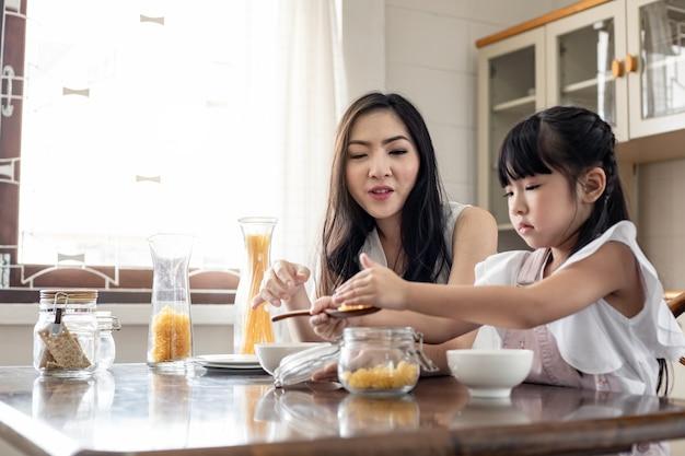 La madre se sienta mirando a la hija que juega en la cocina.